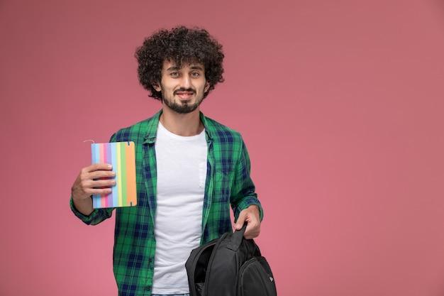 彼のノートとバッグを示す正面図の若い男