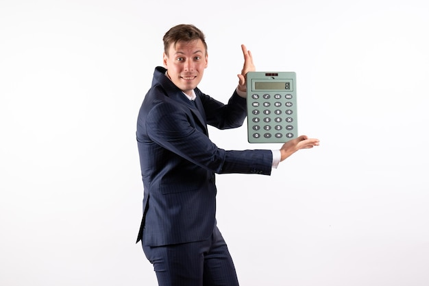 Front view young man in elegant classic suit holding huge calculator on white background