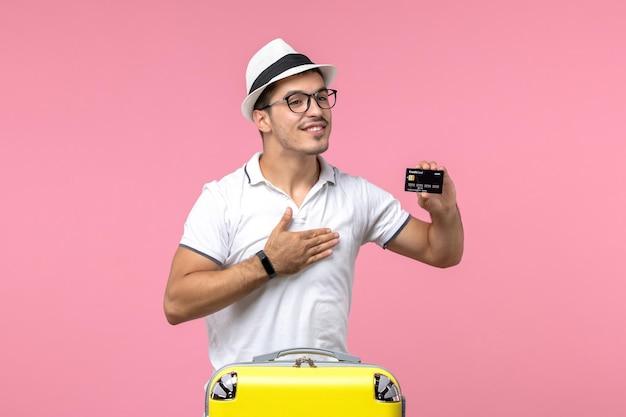 Vista frontale del giovane che tiene emotivamente la carta di credito sulla parete rosa