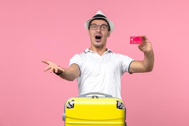 Vista frontale del giovane che tiene emotivamente la carta di credito in vacanza sul muro rosa chiaro light