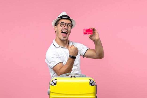 Vista frontale del giovane che tiene emotivamente la carta di credito in vacanza sulla parete rosa