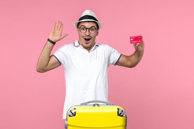 Front view of young man emotionally holding bank card on vacation on pink wall