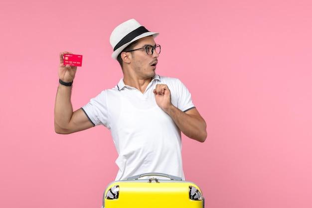 Vista frontale del giovane che tiene emotivamente la carta di credito in vacanza sulla parete rosa Foto Gratuite