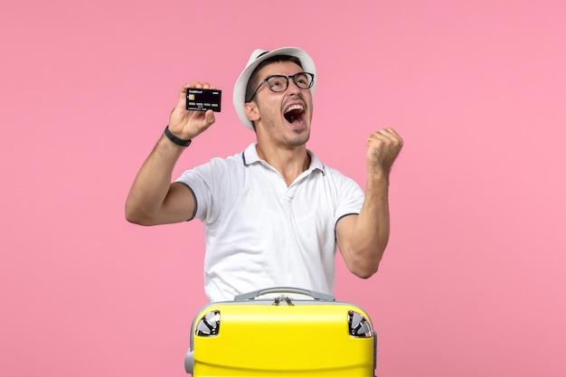Vista frontale del giovane che tiene emotivamente la carta di credito nera sul muro rosa chiaro