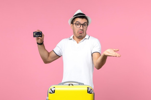 Front view of young man emotionally holding black bank card on a pink wall