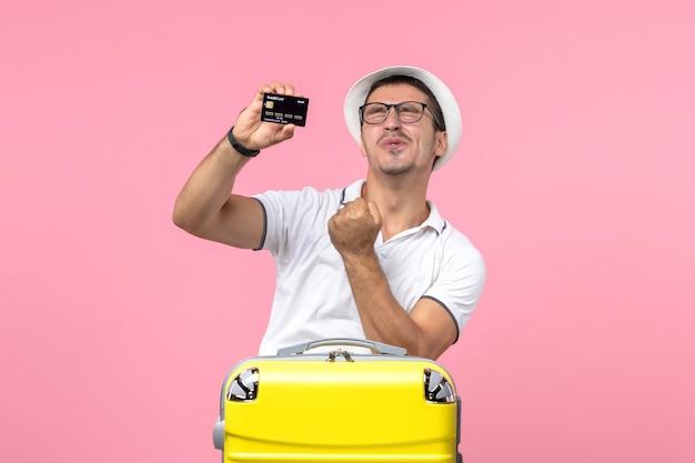 Vista frontale del giovane che tiene emotivamente la carta di credito nera sul muro rosa