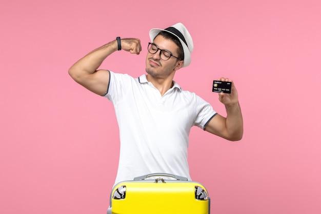 Vista frontale del giovane che flette e tiene in mano una carta bancaria nera sul muro rosa