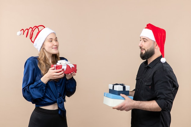 Front view of young man giving christmas presents to woman on pink wall