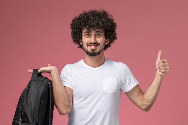 Front view young man giving thumbs up and holding school backpack