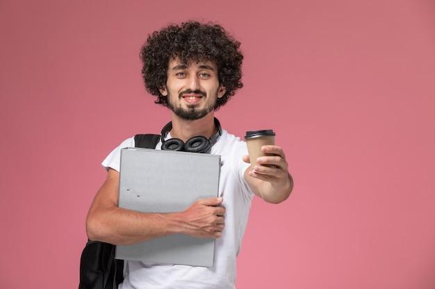 Вид спереди молодой человек дает вам кофе и держит переплет