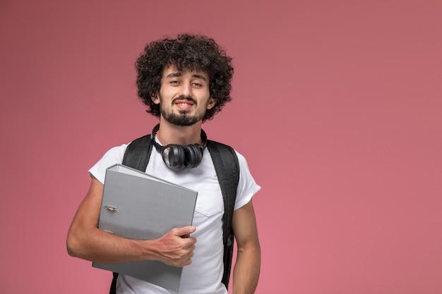 バインダーとヘッドフォンで大学に行く正面図の若い男