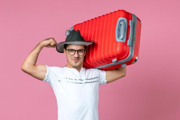 Vista frontale del giovane che va in vacanza e tiene in mano una borsa rossa sul pavimento rosa