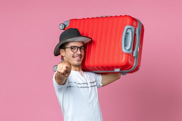 Vista frontale del giovane che va in vacanza e tiene in mano una borsa rossa sul muro rosa