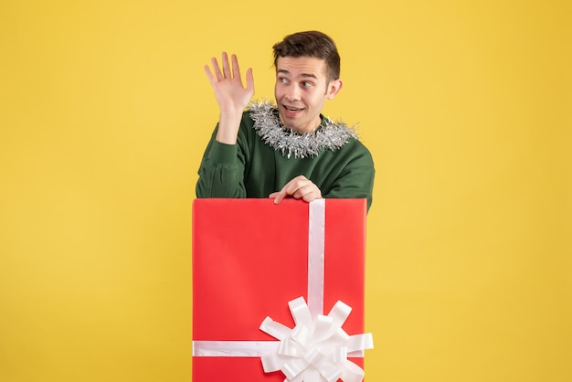 Front view young man hailing someone standing behind big giftbox on yellow