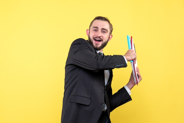 Front view of young man happy businessman holding his folders aside to the left on yellow