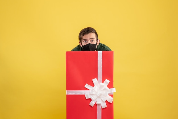 Front view young man hiding behind big giftbox on yellow