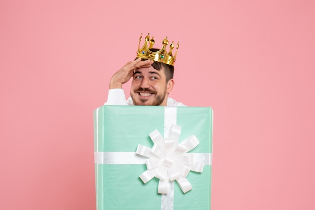 Vista frontale del giovane che si nasconde all'interno della scatola attuale con corona sulla parete rosa