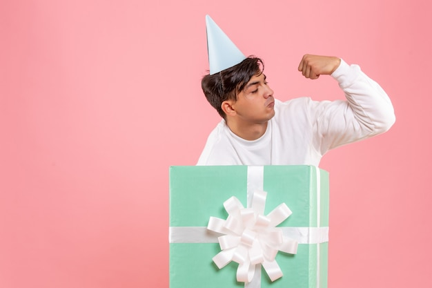 Front view of young man hiding inside present flexing on pink wall