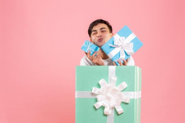 Vista frontale del giovane che si nasconde all'interno del presente e che tiene altri regali sulla parete rosa