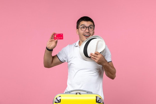 Vista frontale del giovane che tiene carta di credito e cappello sulla parete rosa chiaro