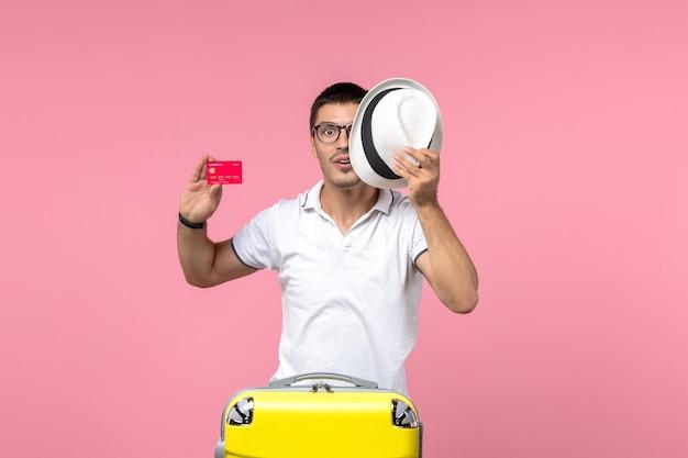 Vista frontale del giovane che tiene carta di credito e cappello sulla parete rosa