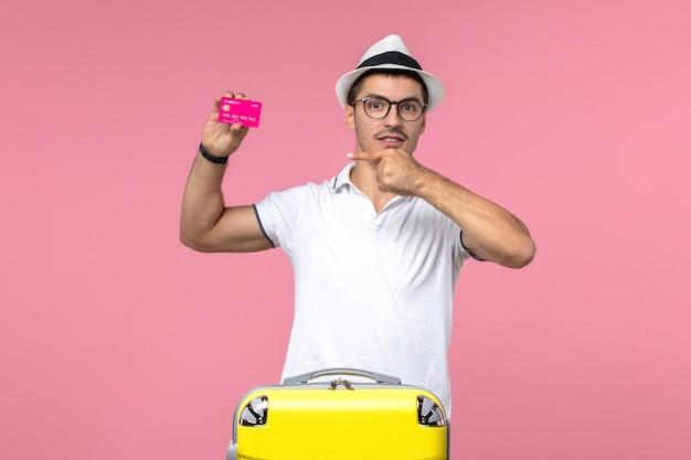 Vista frontale del giovane che tiene la carta di credito sul muro rosa