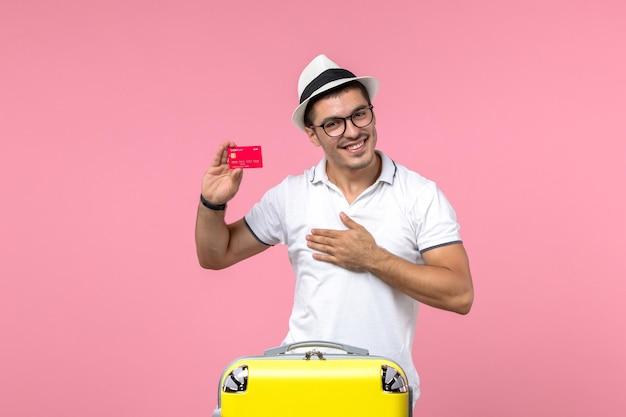 Vista frontale del giovane che tiene la carta di credito e sorride sul muro rosa Foto Gratuite