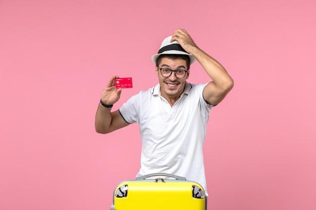 Vista frontale del giovane che tiene la carta di credito e sorride sul muro rosa
