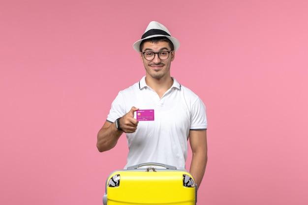 Vista frontale del giovane che tiene la carta di credito durante le vacanze estive sulla parete rosa chiaro