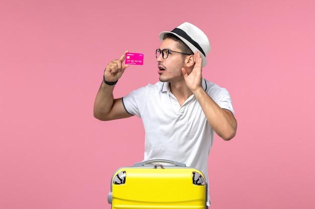Vista frontale del giovane che tiene la carta di credito durante le vacanze estive ascoltando da vicino sul muro rosa