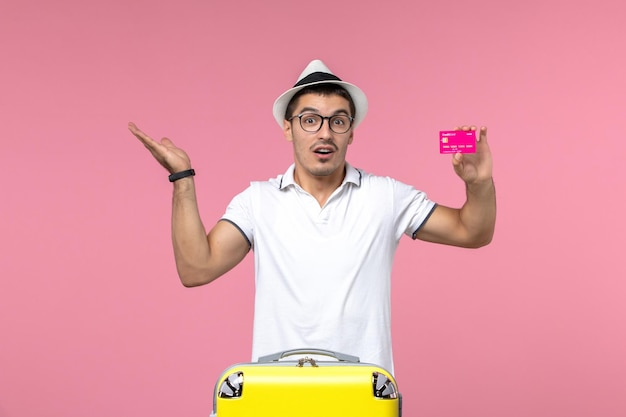 Front view of young man holding bank card on summer vacation on a pink wall