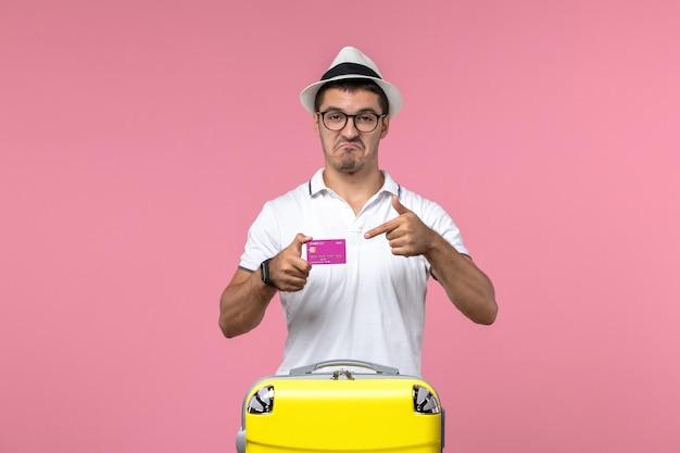 Vista frontale del giovane che tiene la carta di credito durante le vacanze estive sulla parete rosa