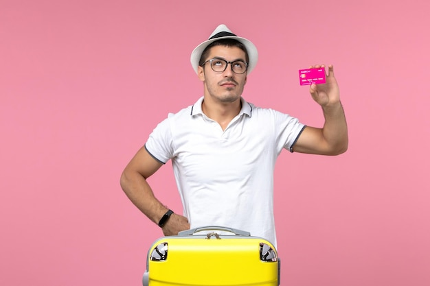 Front view of young man holding bank card on summer vacation on the pink wall