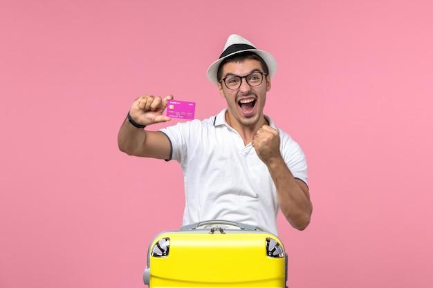 Vista frontale del giovane che tiene la carta di credito durante le vacanze estive e si rallegra sulla parete rosa