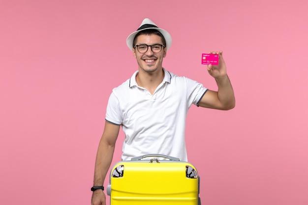 Vista frontale del giovane che tiene la carta di credito durante le vacanze estive che sorride sulla parete rosa