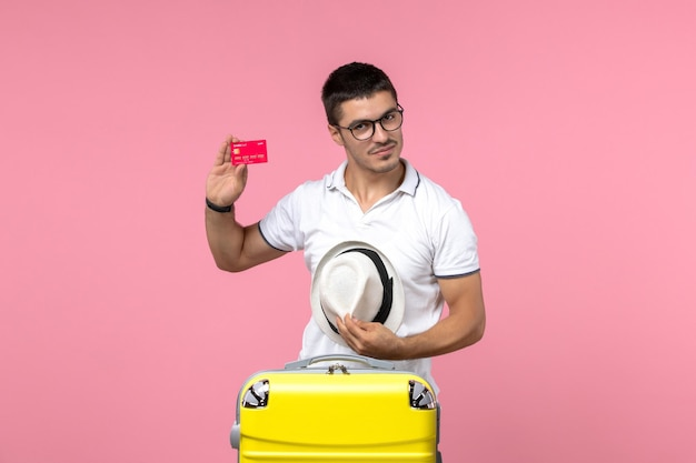 Front view of young man holding bank card and taking off his hat on pink wall