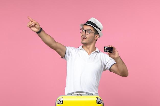 Vista frontale del giovane che tiene la carta di credito in vacanza sul muro rosa