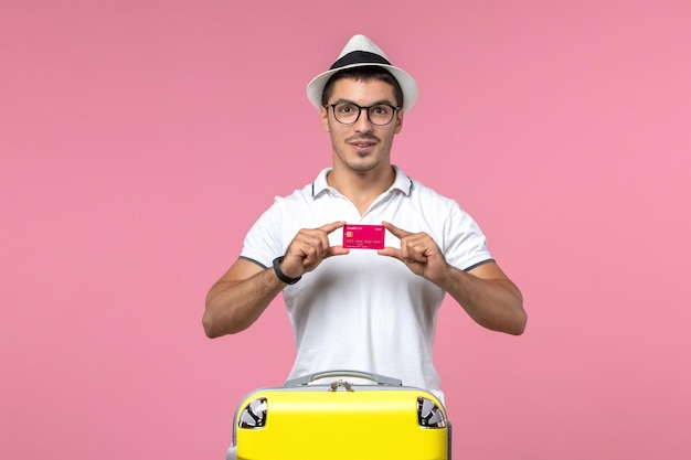 Front view of young man holding bank card on vacation on a pink wall
