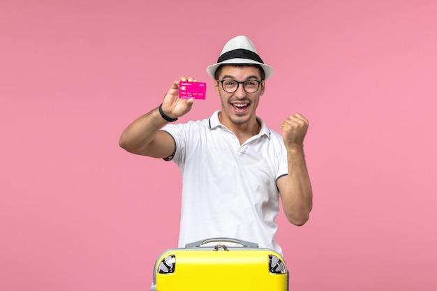 Vista frontale del giovane che tiene la carta di credito con la faccia esultante sul muro rosa