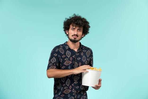 Vista frontale del giovane uomo che tiene il cestino con cips su sfondo azzurro film cinematografico a distanza