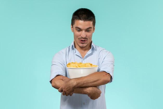 青い壁のフィルムリモート映画シネマ劇場男性のcipsとバスケットを保持している正面図若い男