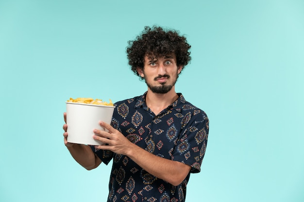 Вид спереди молодой человек, держащий корзину с чипсами на голубой стене, кинотеатр, кинотеатр, удаленный театр