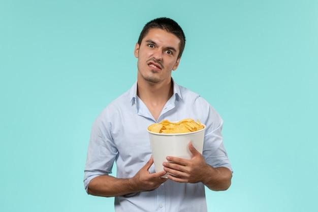 Вид спереди молодой человек, держащий корзину с чипсами на голубой стене, удаленный кинотеатр