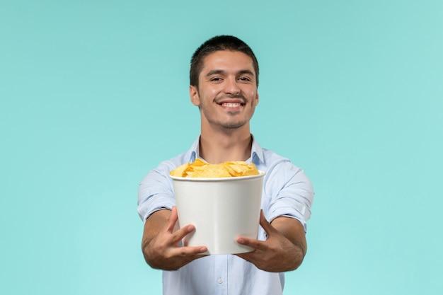 Вид спереди молодой человек, держащий корзину с чипсами на голубой стене, фильм удаленного кино, кинотеатр, мужчина