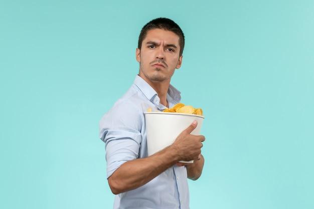 Вид спереди молодой человек, держащий корзину с чипсами на голубой стене удаленного кинотеатра