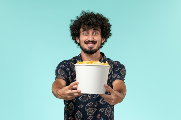 Front view young man holding basket with cips and smiling on a blue wall film cinema movie remote theater