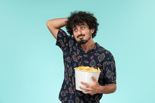 Вид спереди молодой человек держит корзину с чипсами, думая на синей стене, кинотеатр, кинотеатр, удаленный кинотеатр
