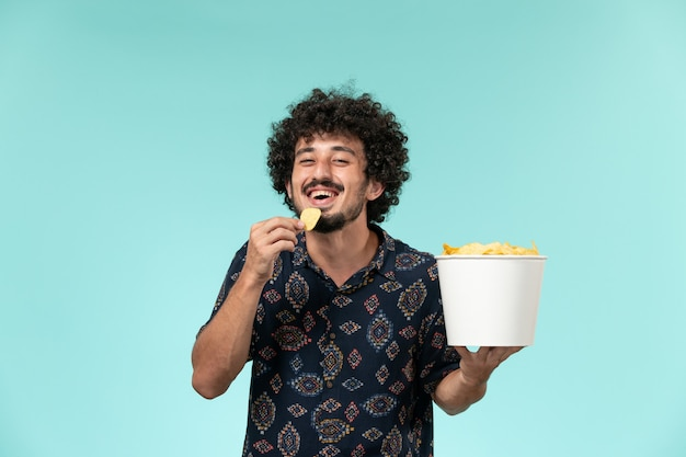 Вид спереди молодой человек держит корзину с картофельными чипсами и ест на голубой стене кинотеатр кинотеатр кинотеатр мужчина