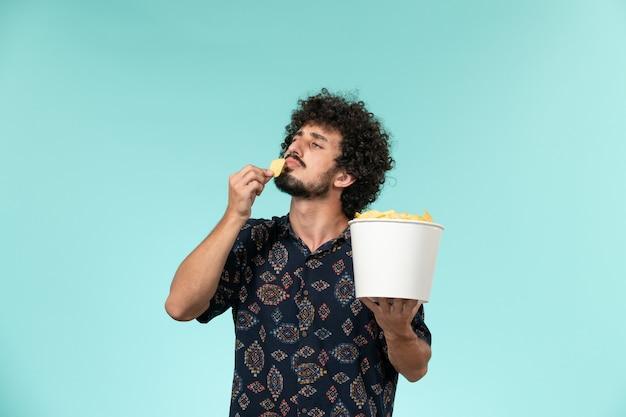 Вид спереди молодой человек держит корзину с картофельными чипсами и ест на синем столе кино фильмы кинотеатр мужчина