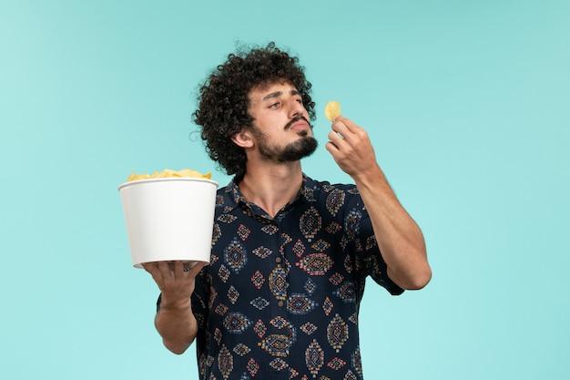 Вид спереди молодой человек держит корзину с картофельными чипсами и ест на синей стене кино фильмы кинотеатр мужчина